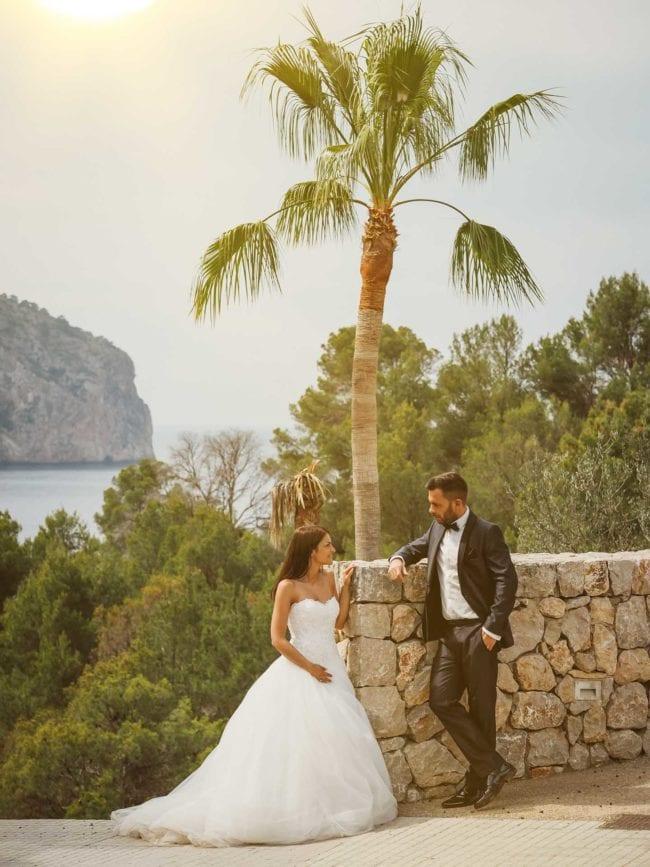 Hochzeitsfoto auf Mallorca n einer Mauer mit Meer und Palmen im Hintergrund